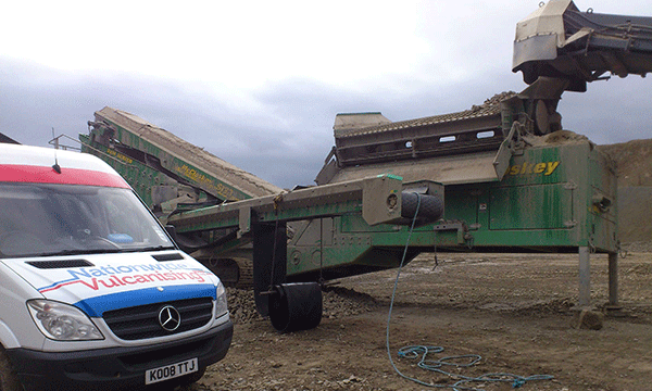 In this image, our van is shown next to a large conveyor system on a quarry site.